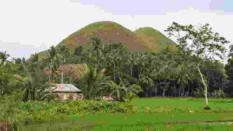 Na base das Colinas de Chocolate, existem casinhas pitorescas e uma enorme área verde - outcast85/Getty Images/iStockphoto