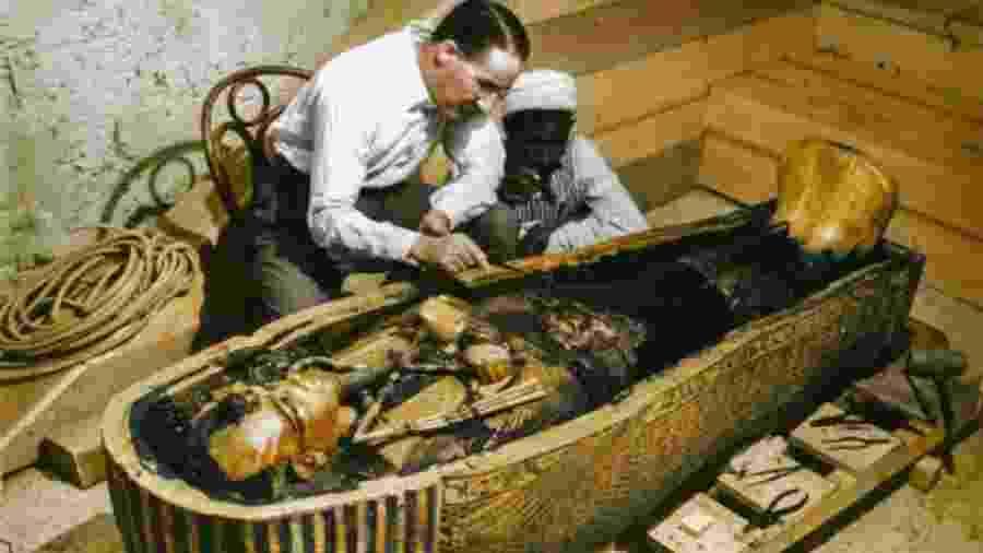 Arqueólogo britânico Howard Carter e um trabalhador egípcio examinam um caixão feito de ouro maciço dentro da tumba - Griffith Institute