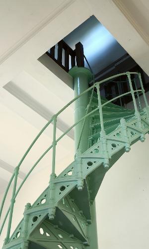 Com ares industriais, a escada caracol tem a estrutura pesada de ferro suavizada pelo verde água. A peça chama atenção no espaço, que tem o branco como base