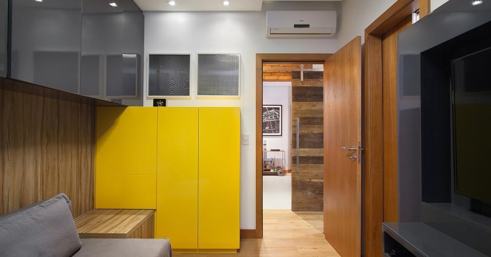 O quarto de hóspedes do Apartamento em Floripa (SC) foi mobiliado de forma que servisse como uma pequena sala íntima. A marcenaria e o sofá-cama solucionaram o quesito flexibilidade. Assim como na área íntima, o piso é de porcelanato padrão madeira, transmitindo sensação de aconchego. Ideia Pimont Arquitetura