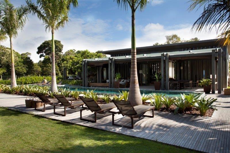 O espaço de lazer da casa de praia em Trancoso (BA) conta com deck de madeira e uma varanda coberta que abriga áreas de estar e jantar. No jardim, destaque para as palmeiras alinhadas junto à piscina. O projeto de arquitetura e paisagismo é uma criação do escritório Debora Aguiar Arquitetos e Associados