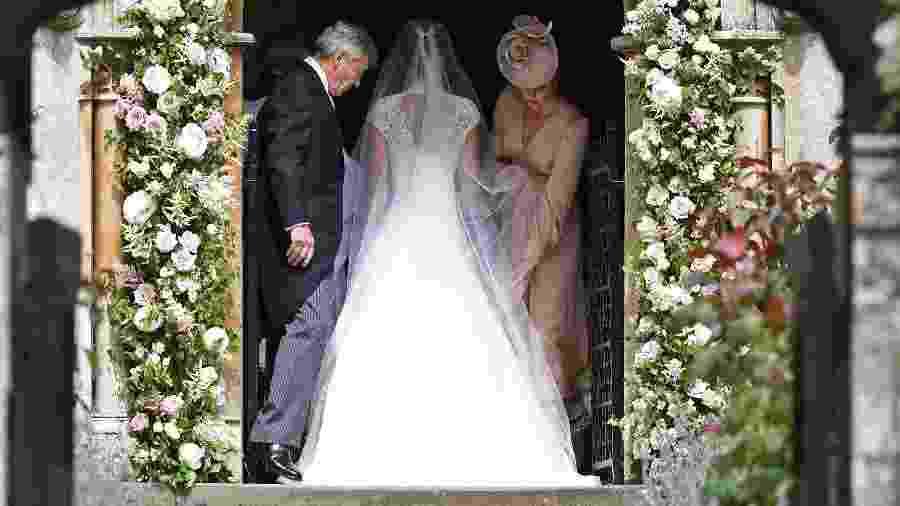 A duquesa de Cambridge ajeita o vestido de noiva de sua irmã, Pippa - AFP