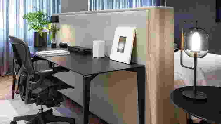 No quarto do casal, o escritório é integrado ao quarto de forma criativa, ideia da arquiteta Consuelo Jorge (https://www.instagram.com/consuelojorge/). Apoiado na cabeceira da cama, de tecido, o office escuro segue a mesma linguagem de todo o amplo cômodo, onde a pintura especial de concreto no forro garante o ar despojado e contrasta com piso de madeira, que aquece e dá conforto. Atrás da mesa, há uma grande estante com objetos e peças de design garimpados pelos moradores. - Divulgação - Divulgação