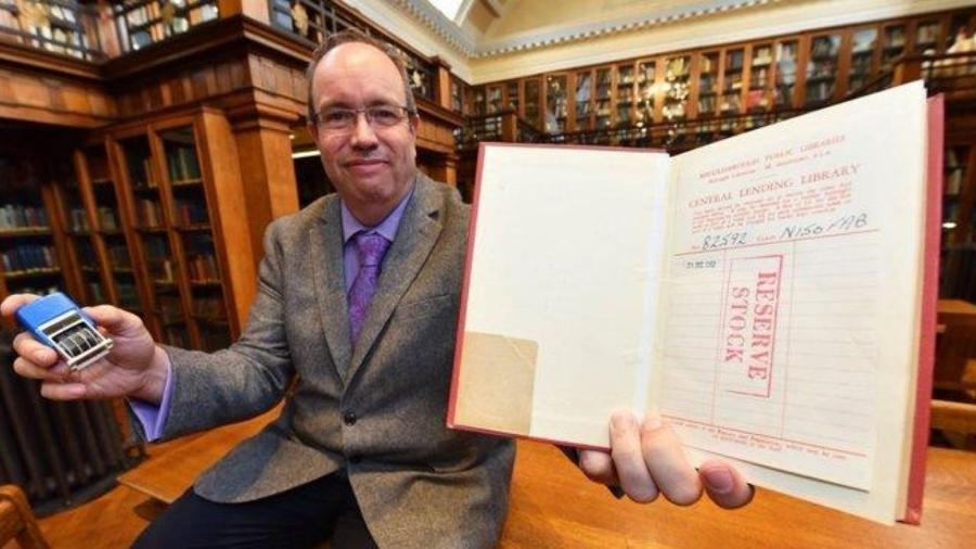 Homem segura o livro que foi devolvido à biblioteca após 57 anos de atraso - Middlesbrought Council