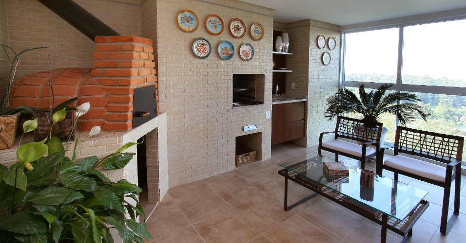 Desenvolvida para um casal com dois filhos, que adora receber, a varanda gourmet assinada por Karina Korn tem tijolos aparentes que remetem ao clima de uma casa de campo. Além da churrasqueira, a arquiteta incluiu no projeto um forno de pizza