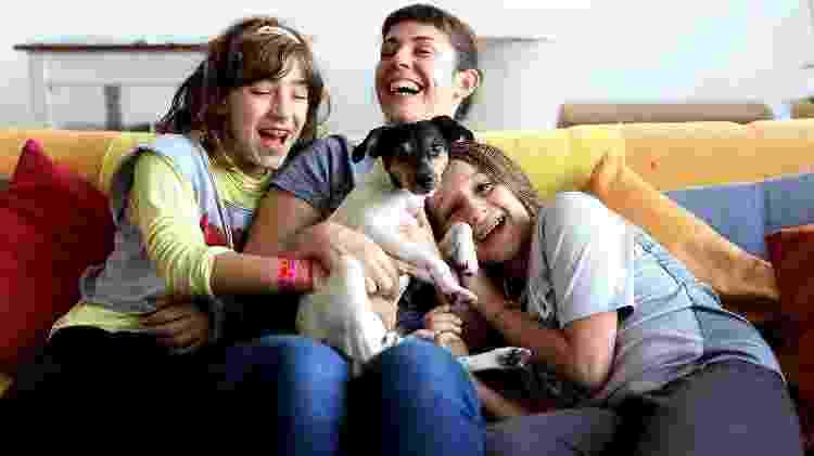 Siva e os filhos no sofá com a cadelinha África. A cachorrinha vai à creche a cada 15 dias - Evelson de Freitas/ UOL - Evelson de Freitas/ UOL