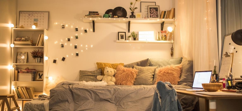 Quarto decorado com luzinhas em cima da cama e na estante de livros - iStockphotos