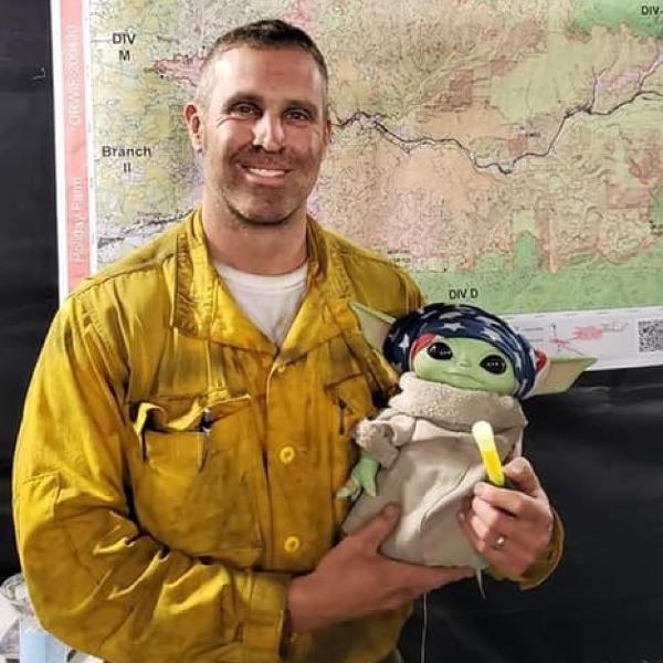 Bombeiro segura boneco do Baby Yoda que está acompanhando oficiais que lutam contra incêndios florestais
