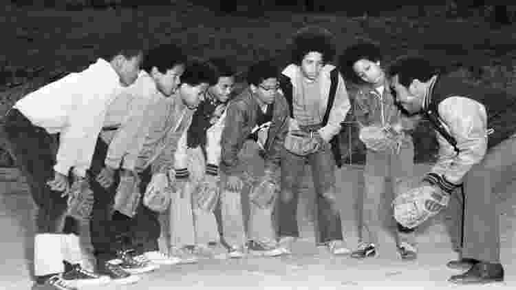 Sete meninos e um homem vestindo jaqueta do time do colégio, usando luvas de beisebol, inclinando-se com as mãos nos joelhos no campo de atletismo, Pittsburgh, Pensilvânia, abril de 1972. - Charles Teenie Harris/Carnegie Museum of Art/Getty Images - Charles Teenie Harris/Carnegie Museum of Art/Getty Images