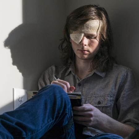 """Carl (Chandler Riggs) escreve carta em cena do nono episódio da oitava temporada de """"The Walking Dead"""" - Divulgação"""