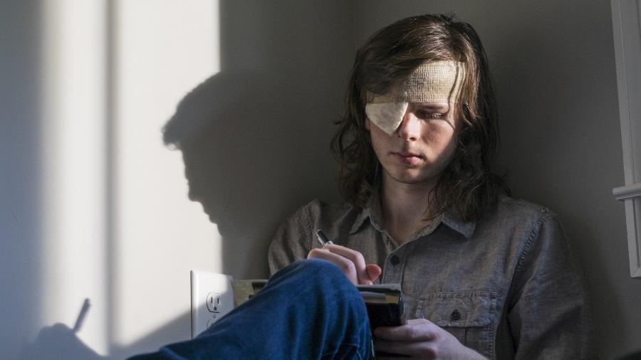 """Carl (Chandler Riggs) escreve cartas em cena do nono episódio da oitava temporada de """"The Walking Dead"""" - Divulgação"""