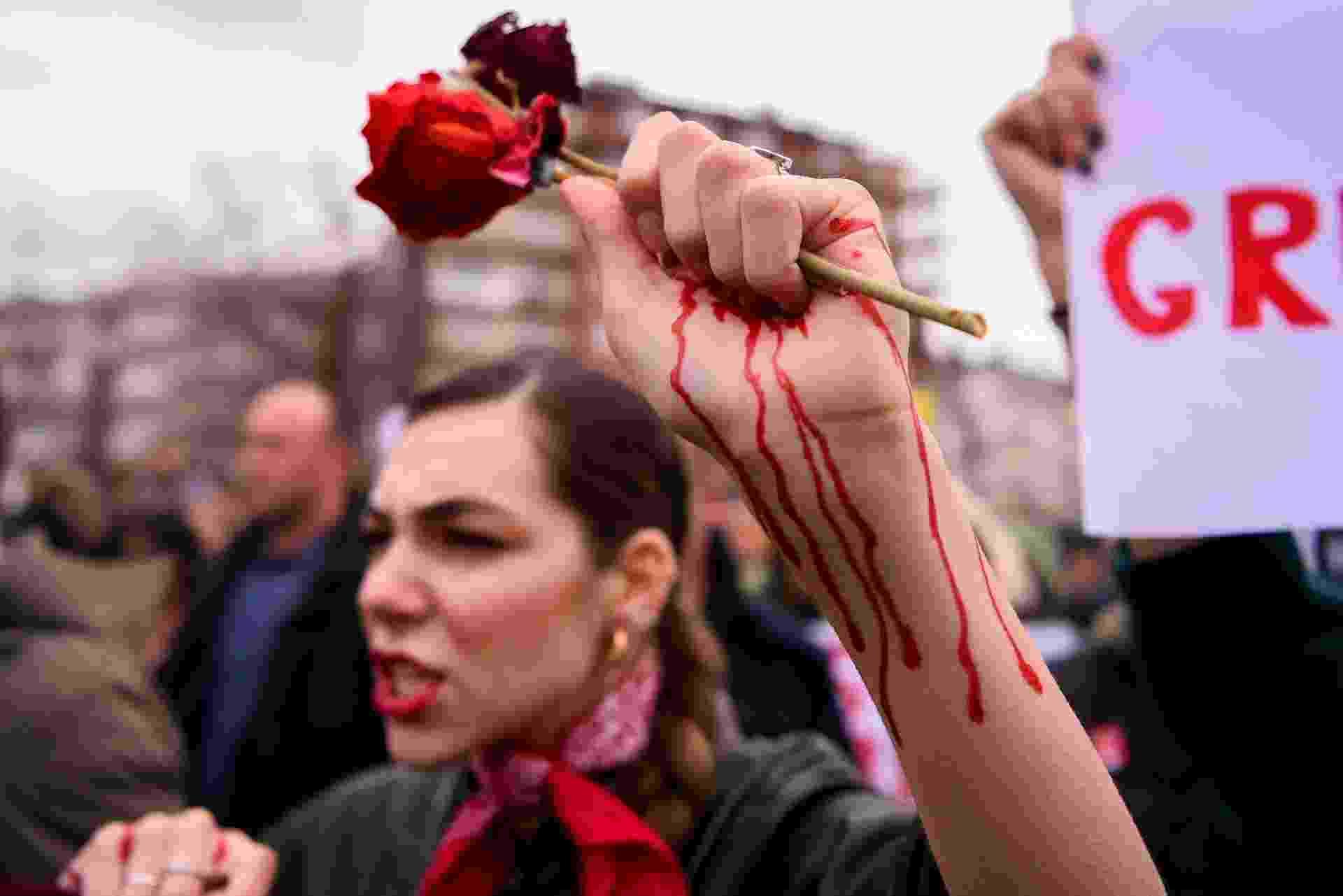 """8.mar.2020 - Mulher segura uma rosa em sua mão """"sangrando"""" durante protesto por igualdade de gênero e contra a violência contra a mulher, no Dia Internacional da Mulher, em Pristina, capital do Kosovo - Armend Nimani/AFP"""