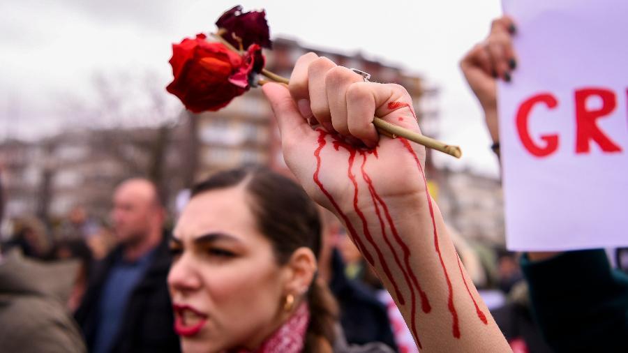 """Mulher segura uma rosa em sua mão """"sangrando"""" durante protesto por igualdade de gênero e contra a violência contra a mulher, no Kosovo - Armend Nimani - 8.mar.2020/AFP"""
