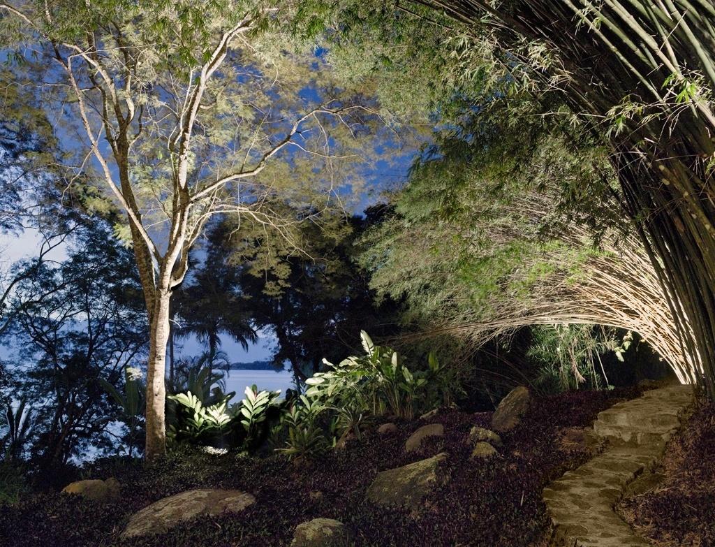 Caminhos de pedra são traçados, respeitando tanto a localização dos bambuzais (Bambusa vulgaris), originais do terreno, como seu declive. O projeto luminotécnico foca os pontos altos, como o angico (Piptadenia paniculata). O sítio fica na Ilha Grande (RJ) e tem projeto de paisagismo assinado por Tania Manela Kurc