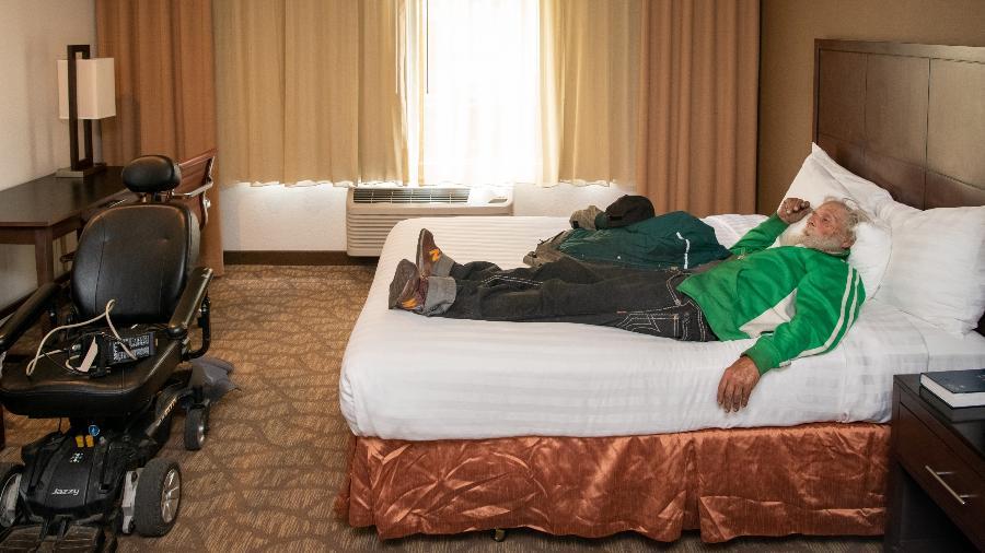 Stephen Shoopman deita na cama de hotel que faz parte do projeto Roomkey em Los Angeles - Michael Owen Baker/Divulgação