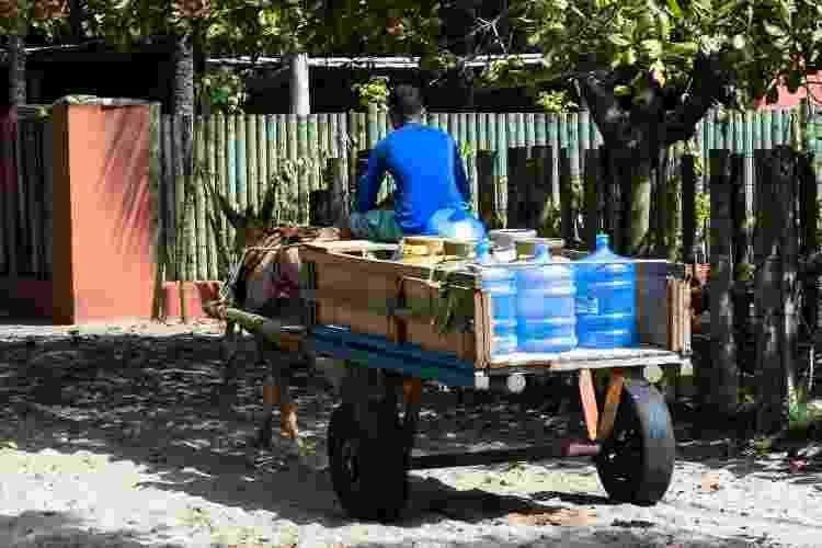 Homem transporta água potável em carroça puxada por jumentos - transporte motorizado é proibido em Caraíva - Getty Images - Getty Images