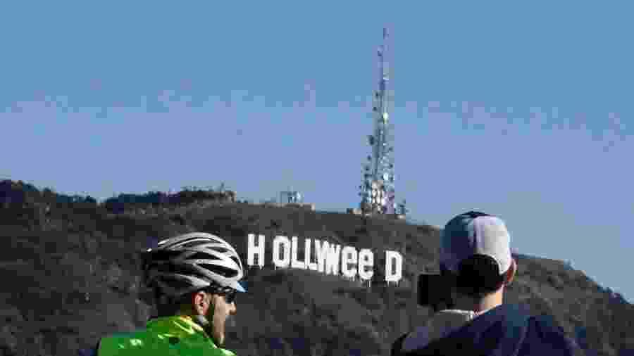 """1.jan.2017 - Curiosos observam o letreiro de Hollywood, tradicional símbolo do cinema, que virou """"Holyweed"""" após brincadeira - Gene Blevins/AFP"""