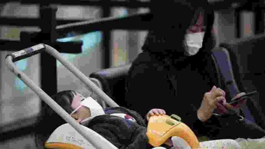 Mulher e criança com máscaras no aeroporto internacional de Tóquio; fábrica de máscaras está trabalhando extra para atender demanda - EPA