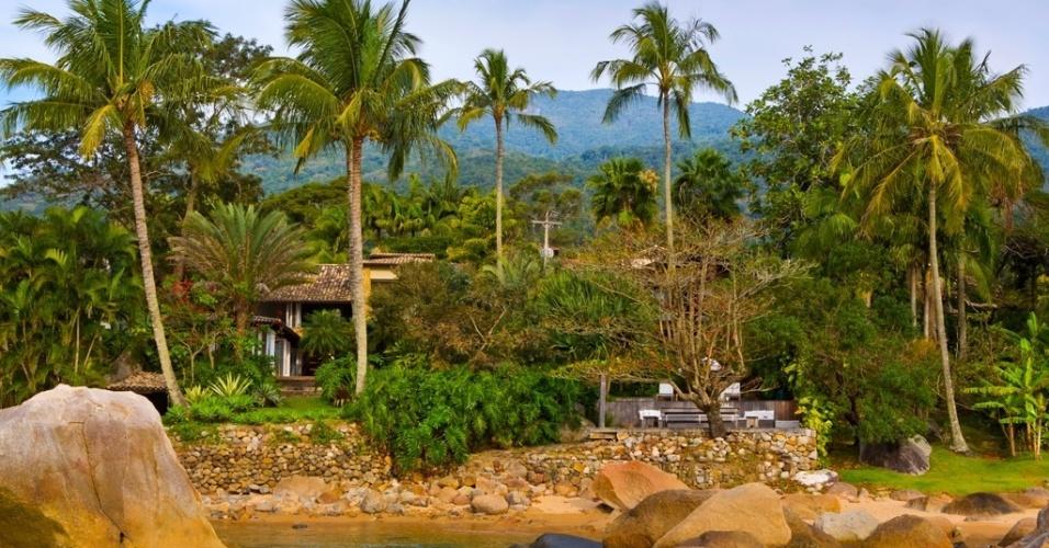 De frente para o mar, o jardim tropical desta casa em Ilhabela (SP) abriga piscinas e decks, além de espécies como palmeiras, coqueiros, helicônias e pândanos