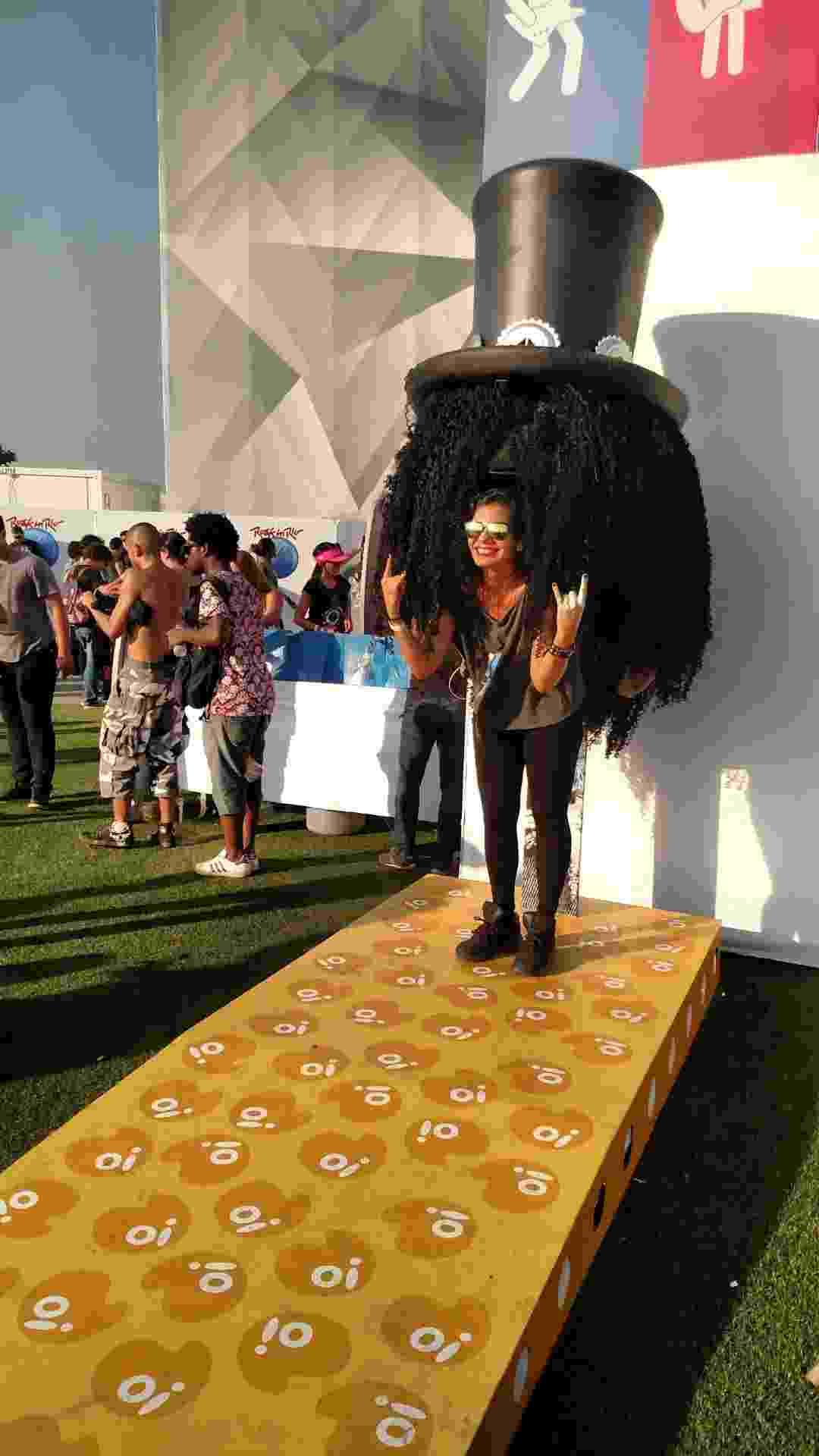 """24.set.2015 - Um orelhão fantasiado de Slash virou febre no Rock in Rio. Os fãs fazem fila para tirar foto no local com a """"cabeleira"""" do ex-guitarrista do Guns N' Roses. """"Gosto muito do Slash. Nunca vi um show dele ao vivo, então aproveitei. Mas estou aqui é para ver o Queens of the Stone Age"""", conta a estagiária Yasmim Burguês, 24 anos - Leonardo Rodrigues/UOL"""