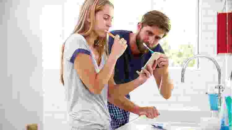 Casal escovando os dentes/ Escovar os dentes com celular - iStock - iStock
