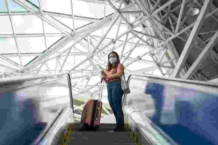 Mulher com máscara em escada rolante de aeroporto - Getty Images - Getty Images