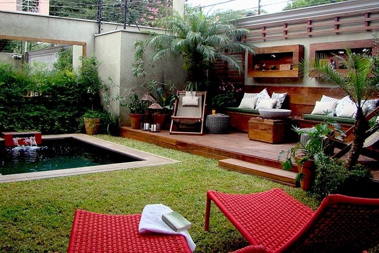 Neste jardim em São Paulo, projetado pela paisagista Gigi Botelho, o chão é parcialmente revestido com grama São Carlos (Axonopus compressus). O ambiente tem decoração acolhedora com espreguiçadeiras de corda, piscina e uma área de descanso sobre o deck de madeira de demolição