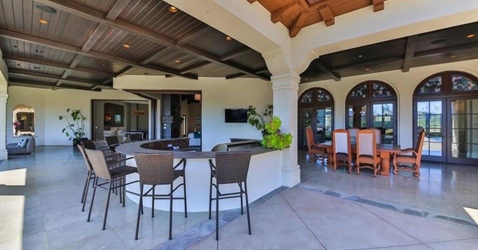 A varanda de Britney Spears conta com bar externo e churrasqueira. Mais atrás (à dir.), é possível ver uma mesa de jantar marrom com seis cadeiras, que permite refeições com vista para o jardim. A residência fica na Califórnia (EUA) e está à venda por R$ 32 milhões