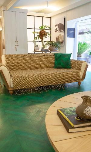 Para criar contraste com o piso de tacões (tauari) verdes e suavizar a composição, os arquitetos Túlio Xenofonte e Fábio Basanie escolheram usar madeiras claras. Um bom exemplo é o banco circular, instalado em volta de um dos pilares do espaço, e o sofá coberto com uma