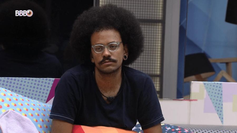"""BBB 21: João Luiz observa o """"Feed BBB"""" na sala de estar - Reprodução/Globoplay"""