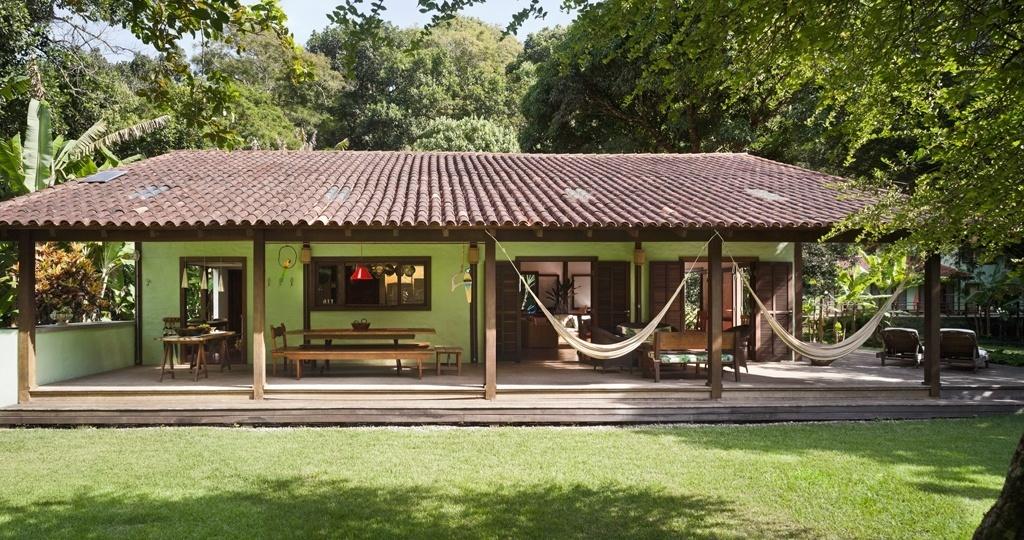 A frente da residência avarandada tem grama esmeralda (Zoyzia japonica), que funciona como transição entre a casa e o jardim tropical assinado pela arquiteta e paisagista Tania Manela Kurc. O projeto de paisagismo para um sítio na Ilha Grande (RJ) venceu a categoria