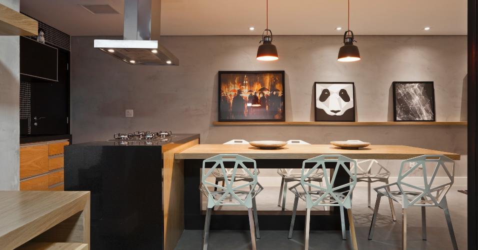 Para esse apartamento pertencente a um jovem economista, a cozinha é completamente aberta e conta com uma ilha de cocção ligada à mesa de jantar, cercada por cadeiras One, com desenho de Konstantin Grcic. Os revestimentos remetem à dureza do concreto e são equilibrados pelo uso da madeira clara. O espaço foi assinado pelo escritório Conrado Ceravolo Arquitetos