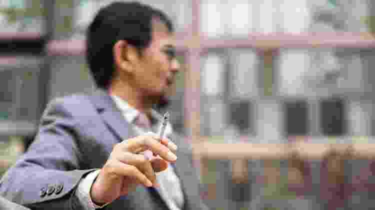 Homem sentado em banco com cigarro na mão - yipengge/Istock - yipengge/Istock