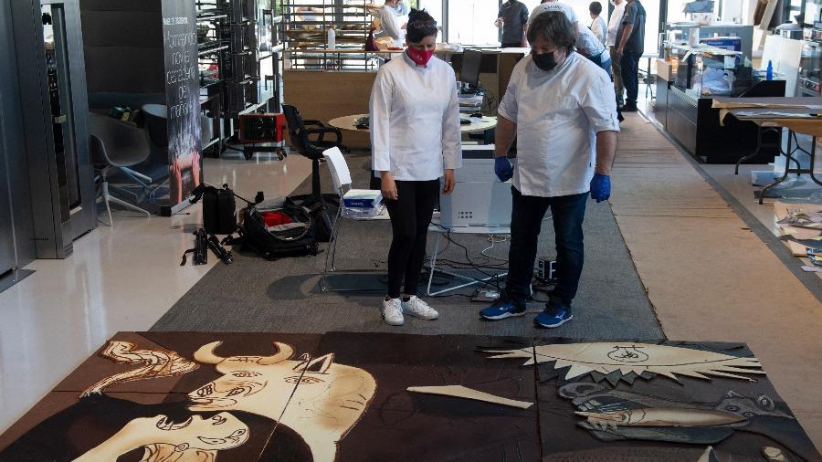 """Dois chocolateiros do grupo Euskal Gozogileak observam versão de chocolate de """"Guernica"""", de Picasso - ANDER GILLENEA / AFP"""