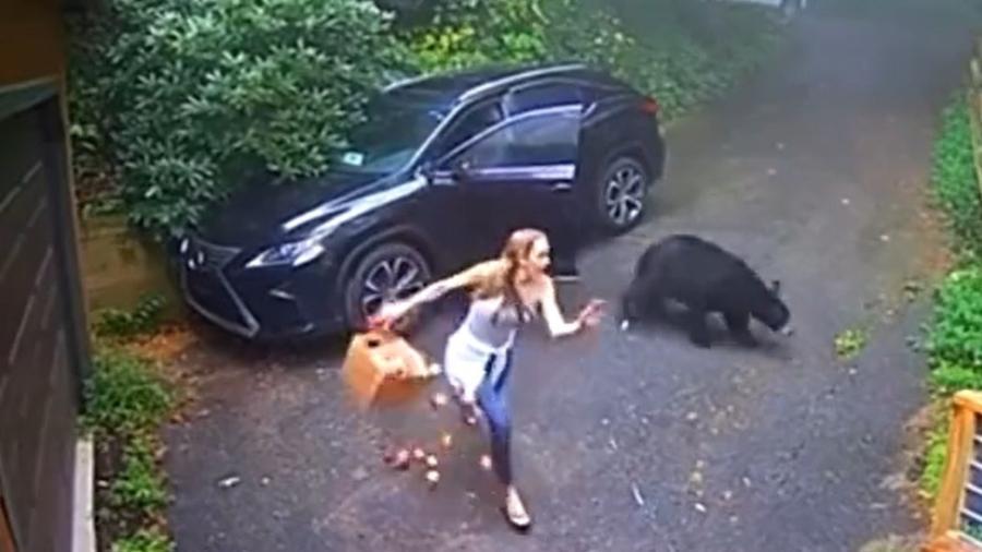 Mulher foge de urso ao abrir porta de carro - Reprodução
