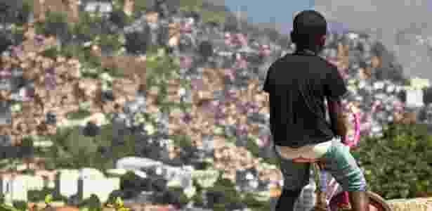 Menino observa o morro da Mineira, no Rio, de sua bicicleta - Lucas Almeida/Divulgação - Lucas Almeida/Divulgação