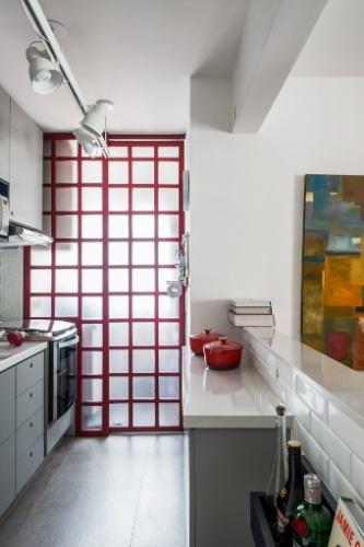 A cozinha ganhou um toque de vivacidade com o vermelho da esquadria da porta de correr, que separa o ambiente da lavanderia. Uma segunda bancada (à dir.), mais baixa, agiliza a rotina da cozinha organizada como um corredor. O apê Caravelas tem projeto de reforma da arquiteta Marcela Madureira