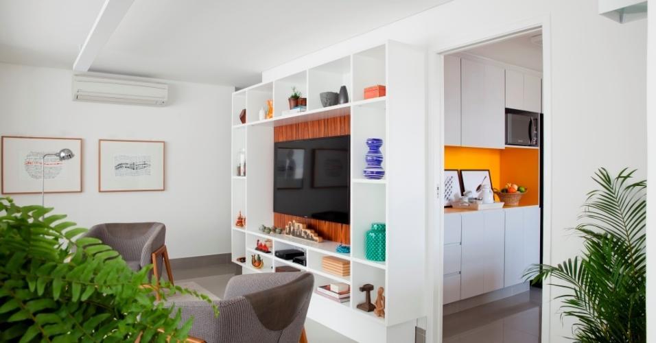 A estante da sala leva MDF laqueado e folha de pau-ferro e é formada por nichos que abrigam os 'souvenires' de viagens da família. A porta para a cozinha é de correr e, quando aberta, é 'engolida' pela parede divisória de gesso acartonado. A luminária de teto (Reka) oferece luz rebatida pelo forro rebaixado