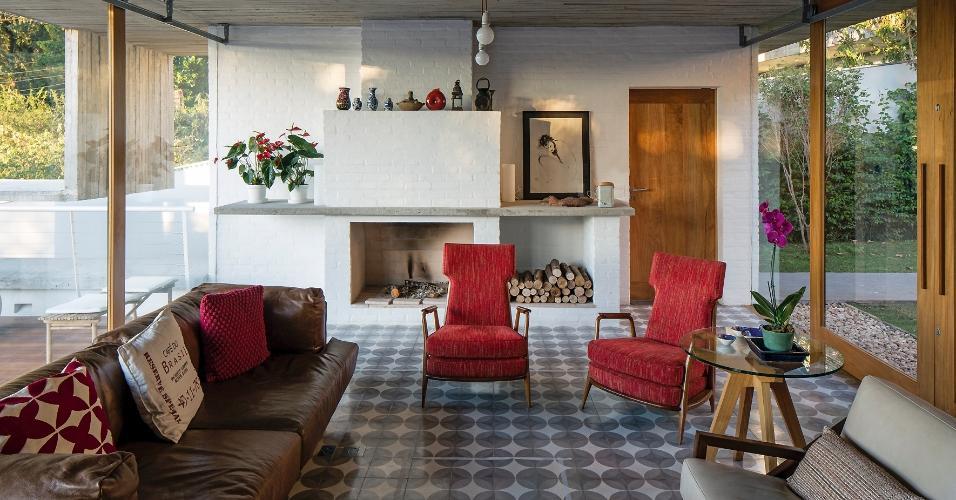 Além de aquecer e dar aconchego ao ambiente, a lareira é o centro das atenções do estar que recebe iluminação natural das duas laterais, onde estão o pátio (à dir.) e o terraço. Na decoração, o mobiliário tem ares dos anos 50, com as poltronas apoiadas em pés palito. A casa Lapa é um projeto do escritório Brasil Arquitetura