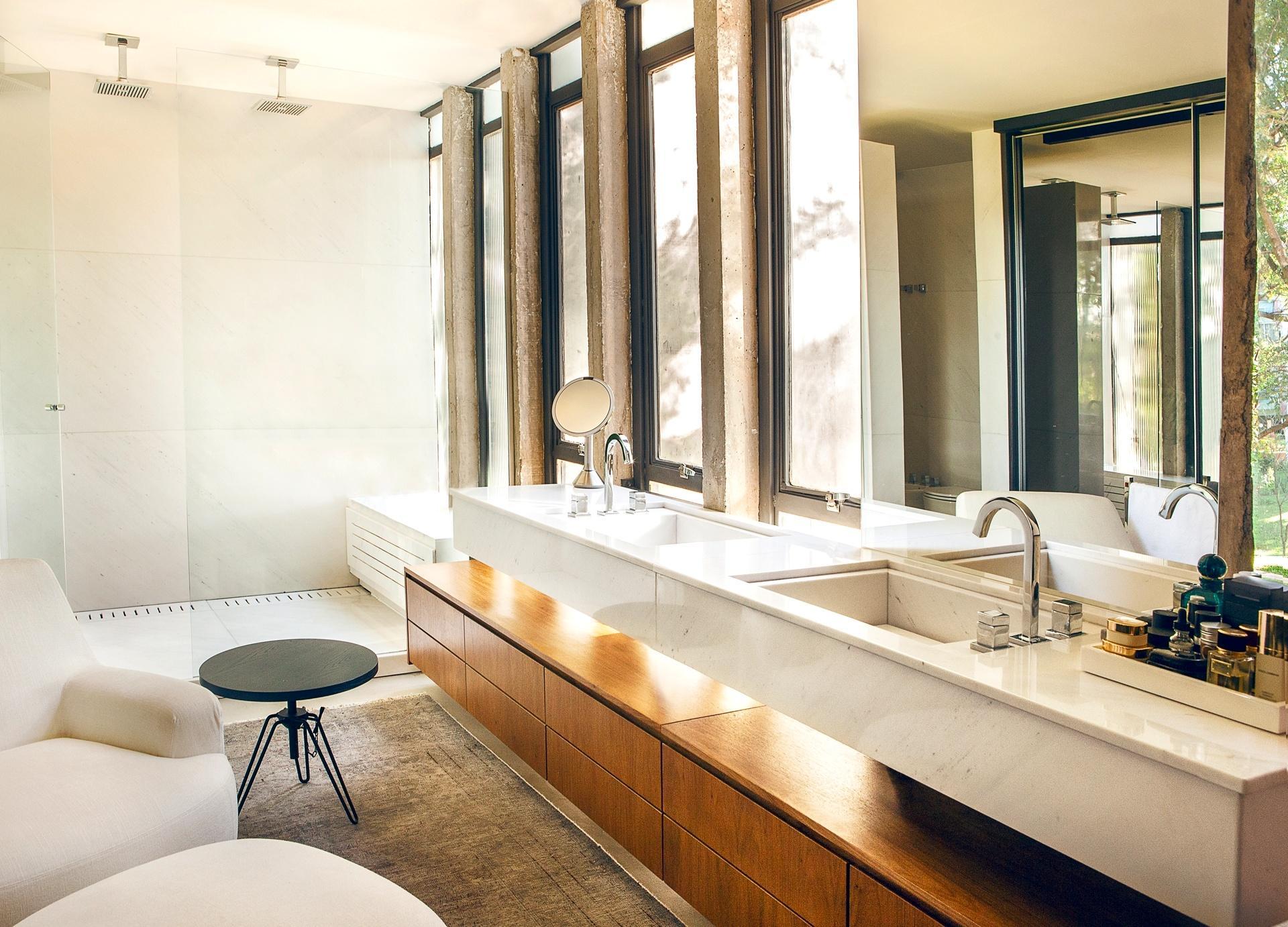 Categoria: Apartamentos - Studio Valéria Gontijo. O apê em Brasília foi reformado, mas teve seus janelões intercalados com colunas de concreto, preservados. No banheiro, sob a bancada com duas cubas, um gabinete generoso. Ainda no espaço, dois chuveiros e uma poltrona garantem o conforto necessário para os momentos de relaxamento