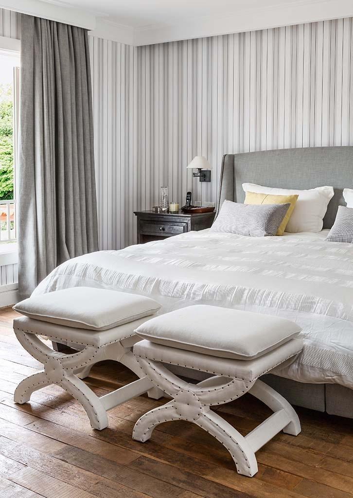 Nesta casa de campo projetada pelo arquiteto Dado Castello Branco, a suíte do casal conta com uma atmosfera elegante e serena dada pelo papel de parede (Paper) listrado e as cortinas de linho, que deixam a ambientação mais atual