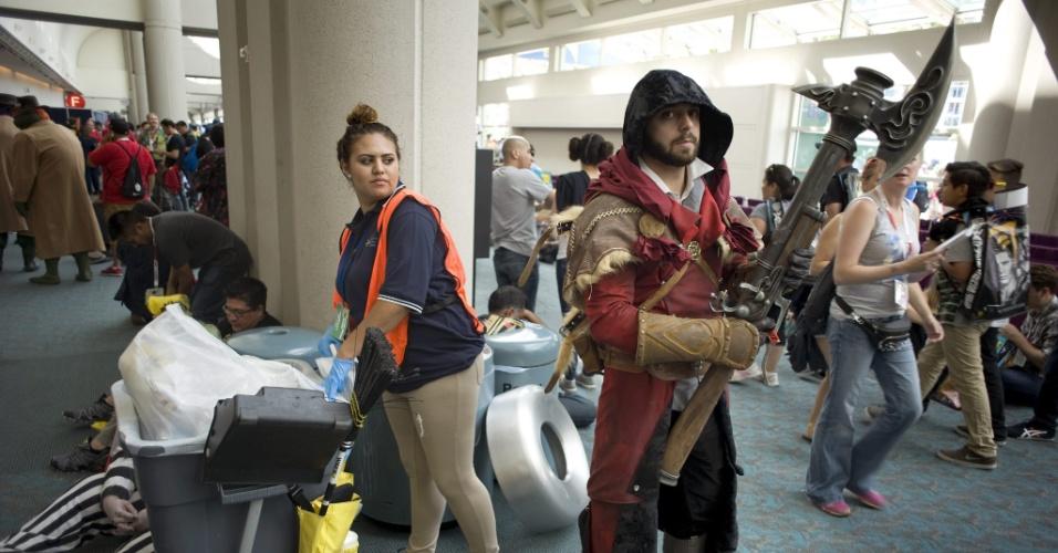 """11.jul.2015 - Igor Pinsky, vestido como um personagem da série de video-games """"Assassin's Creed"""", espera no lobby do Centro de Convenções de San Diego enquanto uma funcionária faz a limpeza do local que recebe a Comic-Con"""