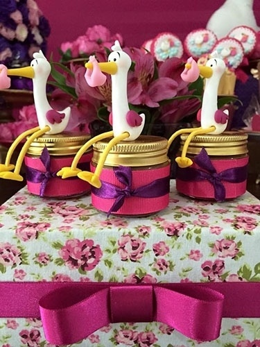 Potinhos de doce de leite decorados com biscuit de cegonha, fitas de gorgurão rosa e cetim roxo estavam sobre a caixa de MDF, forrada com tecido floral. Os elementos ajudaram a dar mais graça ao chá de fraldas