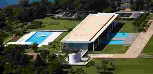 Vista aérea do conjunto do Palácio da Alvorada com o Lago Paranoá, ao fundo. O complexo é constituído de capela, edifício principal, piscina e anexo semi-enterrado, que abriga as dependências de serviços e uma sala de cinema. À direita, um detalhe: o corredor de palmeiras imperiais definido por Orcar Niemeyer, a pedido do presidente Juscelino Kubitschek - Leonardo Finotti/ UOL - Leonardo Finotti/ UOL