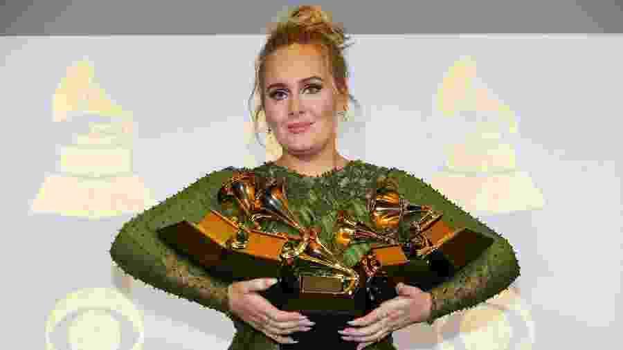 Adele carrega os cinco Grammys que ganhou na noite: álbum do ano, gravação do ano, música do ano, melhor performance solo e melhor álbum vocal pop - Mike Blake/Reuters