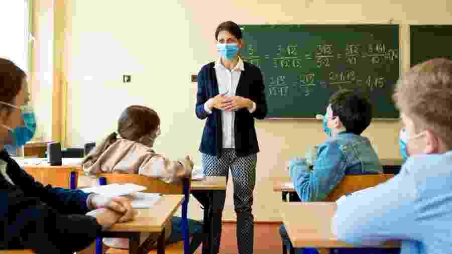 Professora em sala de aula com máscara de proteção facial em meio à pandemia do coronavírus - iStock