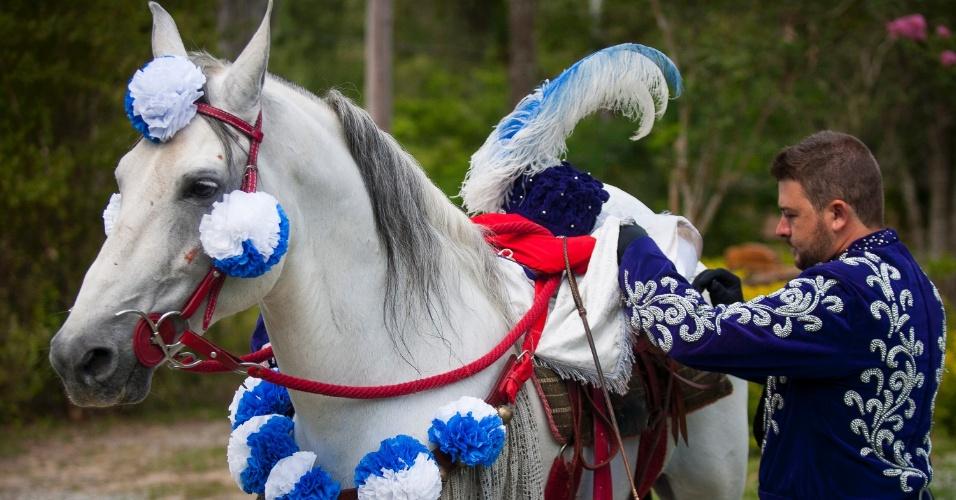 8.jan.2016 - Cavaleiro coloca adereço em seu cavalo para sair pelas ruas de Bonfim onde acontece o Carnaval a Cavalo