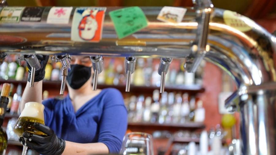 Bartender com máscara e luvas em Bolzano, na Itália - Alessio Coser/Getty Images
