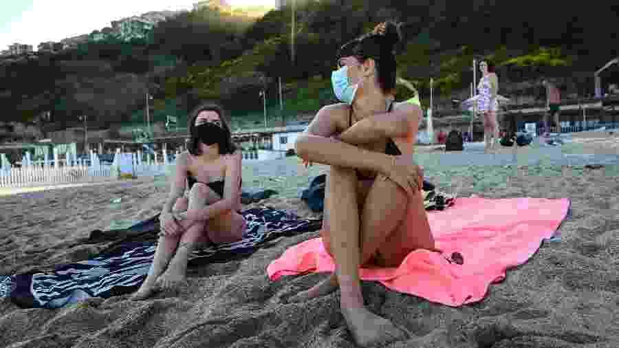 Mulheres aproveitam os dias de calor em praia na Itália com máscaras de proteção - Getty Images
