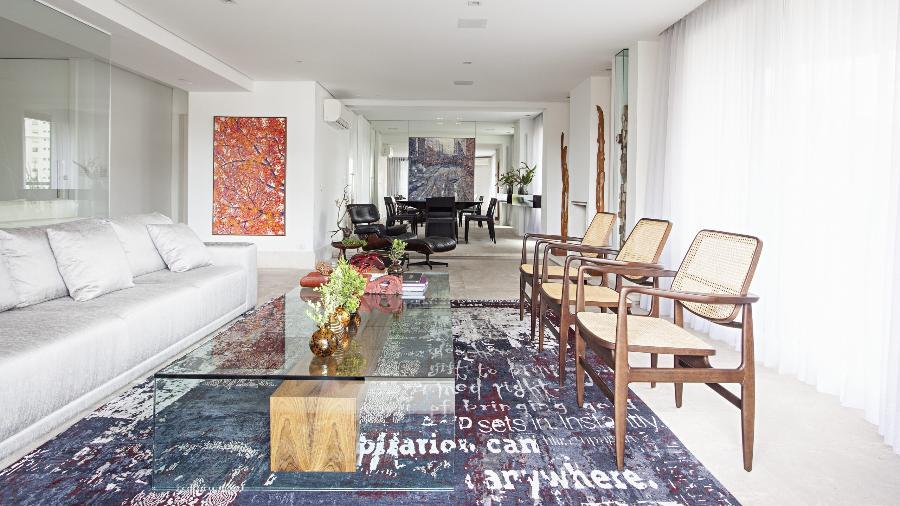Nesse projeto do Korman Arquitetos, o tapete de origem nepalesa traz um aspecto desgastado e palavras estampadas, conferindo descontração ao estar com piso de travertino rústico - Gui Morelli